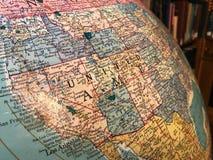 Parte do globo da terra com um mapa pol?tico no fundo dos livros foto de stock