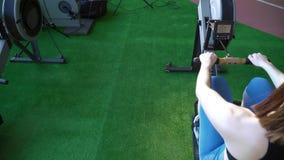 A parte do sportwoman que aquece-se na máquina de enfileiramento no gym verde filme