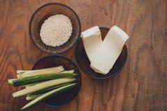 Parte dos ingredientes para preparar o sushi nas placas na tabela, a saber arroz, queijo derretido, pepinos e caranguejo imagem de stock royalty free