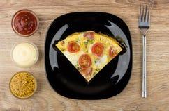 Parte dos ovos fritos com salsicha, tomates na placa preta Imagens de Stock Royalty Free