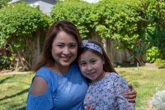 Parte externa de sorriso e de riso da mãe e da filha de Latina no pátio traseiro fotografia de stock