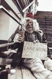 Parte externa do mendigo desesperado e cartaz de assento da escrita que pede a ajuda foto de stock