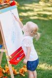 Parte externa ereta da menina da criança da criança no desenho do parque do outono do verão na armação com os marcadores que olha Fotografia de Stock Royalty Free