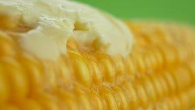 Parte fresca saboroso de manteiga que derrete no milho fresco amarelo maduro em espigas filme