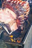 Parte grande de carne cocinada en para girar la parrilla sobre el fuego abierto Grilled preparó aire libre Jamón viejo asado a la foto de archivo libre de regalías