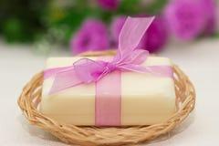 Parte grande de sabão bege no busket, curva roxa do witn, flores em b Imagem de Stock Royalty Free