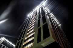 Parte inferior de la visión para arriba en un edificio moderno alto en la noche imagenes de archivo