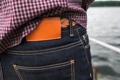 Parte inferior del cuerpo de hombres, del bolsillo trasero de vaqueros y de la etiqueta para un comercia Imágenes de archivo libres de regalías