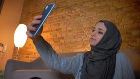Parte inferior del primer encima del lanzamiento del adolescente femenino musulmán atractivo joven que toma selfies en el teléfon metrajes