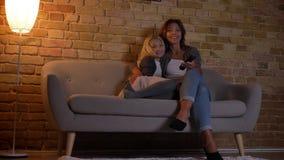 Parte inferior do close up acima do tiro da mulher caucasiano nova e sua da filha que olham a tevê com excitamento filme