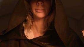 Parte inferior do close-up da cara do mágico da menina em uma sala escura com luz de vela que sorri do flash abaixo Baixa chave video estoque