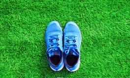 Parte le scarpe da tennis di sport del blu sui precedenti strutturati dell'erba verde Fotografie Stock Libere da Diritti