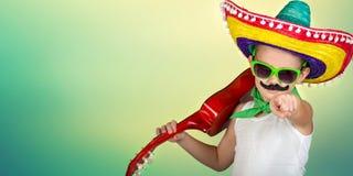 Parte mexicana Muchacho con un bigote falso en un sombrero que toca la guitarra fotografía de archivo libre de regalías