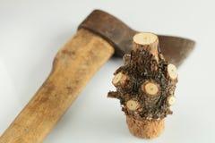 Parte nodal de um tronco de árvore com ramos cortados e um machado velho em um fundo branco Imagem de Stock