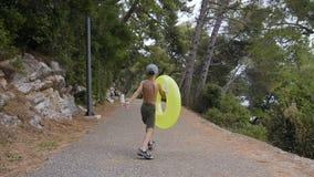 Parte posterior de la visión Un niño pequeño en pantalones cortos con el flotador inflable alegre que corre a lo largo del parque almacen de metraje de vídeo
