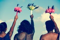 Parte posterior de las mujeres afroamericanas que sostienen ramos coloridos en el aire el día de boda imagen de archivo libre de regalías