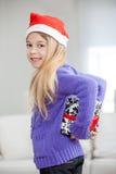 Parte posterior de ocultación sonriente del regalo de Navidad de la muchacha detrás Imagenes de archivo