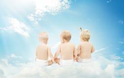 Parte posterior del bebé en los pañales que se sientan en las nubes sobre fondo del cielo foto de archivo