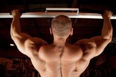 Parte posterior del Bodybuilder en sitio del entrenamiento Foto de archivo libre de regalías
