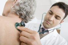 Parte posterior del doctor Checking Patient usando el estetoscopio fotografía de archivo libre de regalías