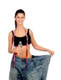 Parte posterior delgada de la mujer con los pantalones y la botella de agua enormes Foto de archivo libre de regalías