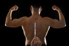 Parte posterior fuerte del deportista joven del culturismo que usa los esteroides para el funcionamiento atlético cada vez mayor  Imagenes de archivo