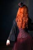 Parte posterior hermosa de la mujer del steampunk Muchacha pelirroja delgada en corsé y sombrero imágenes de archivo libres de regalías