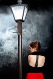 Parte posterior noir de la niebla de la linterna de la calle de la muchacha del cine imagenes de archivo
