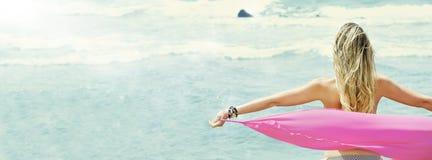 Parte posterior rubia de la mujer joven con los brazos abiertos, tomando un paño de seda que mira el mar Imagenes de archivo