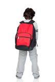 Parte posteriore anonima del bambino con un pacchetto pesante Fotografia Stock
