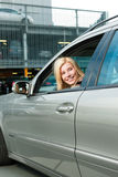 Parte posteriore della donna la sua automobile ad un livello di parcheggio Fotografia Stock Libera da Diritti