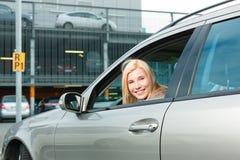 Parte posteriore della donna la sua automobile ad un livello di parcheggio Fotografie Stock Libere da Diritti