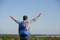 Parte posteriore della foto dell'uomo turistico con lo zaino, mani su sulla collina nel fondo delle estensioni della montagna, ci fotografia stock libera da diritti