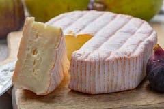 Parte redonda de queijo francês Fleur Rouge feita do leite de vaca servido como a sobremesa com figos e as peras frescos foto de stock royalty free