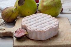 Parte redonda de queijo francês Fleur Rouge feita do leite de vaca servido como a sobremesa com figos e as peras frescos fotografia de stock royalty free