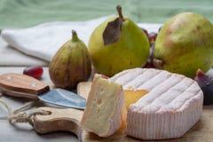 Parte redonda de queijo francês Fleur Rouge feita do leite de vaca servido como a sobremesa com figos e as peras frescos imagem de stock royalty free
