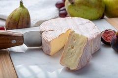 Parte redonda de queijo francês Fleur Rouge feita do leite de vaca servido como a sobremesa com figos e as peras frescos foto de stock