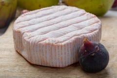 Parte redonda de queijo francês Fleur Rouge feita do leite de vaca servido como a sobremesa com figos e as peras frescos fotos de stock