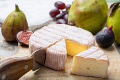 Parte redonda de queijo franc?s Fleur Rouge feita do leite de vaca servido como a sobremesa com figos e as peras frescos foto de stock royalty free