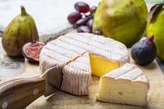 Parte redonda de queijo franc?s Fleur Rouge feita do leite de vaca servido como a sobremesa com figos e as peras frescos imagens de stock royalty free