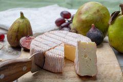 Parte redonda de queijo franc?s Fleur Rouge feita do leite de vaca servido como a sobremesa com figos e as peras frescos imagens de stock