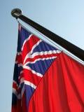 Parte retroiluminada de la bandera roja, volada de un megayacht Foto de archivo libre de regalías