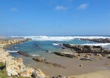 Parte rocciosa della spiaggia della baia della Sardegna a Port Elizabeth, Sudafrica Fotografia Stock Libera da Diritti