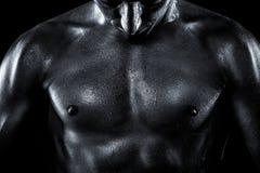 Parte suando do corpo dos homens em um backgro preto Fotografia de Stock Royalty Free