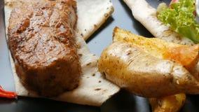 Parte suculenta deliciosa de bife da carne de porco com batatas e vegetais em uma placa preta à moda no restaurante vídeos de arquivo