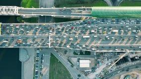 A parte superior aérea disparou para baixo do tráfego rodoviário congestionado pesado e de trem da periferia movente nas horas de fotos de stock