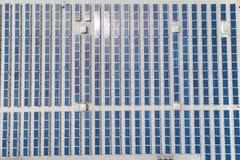 A parte superior aérea vê para baixo em muitas fileiras dos painéis solares alinhadas sobre do telhado da fábrica fotos de stock