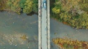 A parte superior aérea vê para baixo o tiro da ponte com o carro e os povos outono, Transcarpathian filme