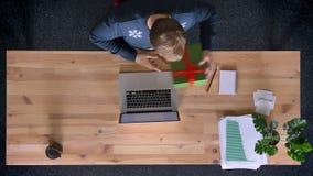 Parte superior abaixo da opinião o homem que trabalha no escritório na frente do portátil que troca presentes com o colega sem ab video estoque