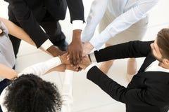 A parte superior acima dos executivos diversos da vista empilhou as mãos foto de stock
